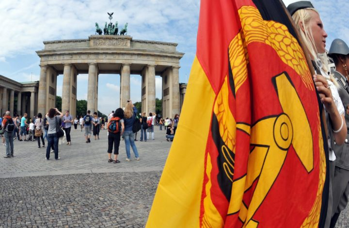 epa02285156 A woman clad in a former East German army uniform holds a former GDR flag on Pariser Platz in front of the landmark Brandenburg Gate in Berlin,Germany, 13 August 2010. Taking photos with GDR flags and GDR memorabilia is popular with Berlin tourists. This 13th of August marks the 49th anniversary of the start of the construction of the Berlin Wall in the former East Berlin in 1961.  EPA/RAINERJENSEN