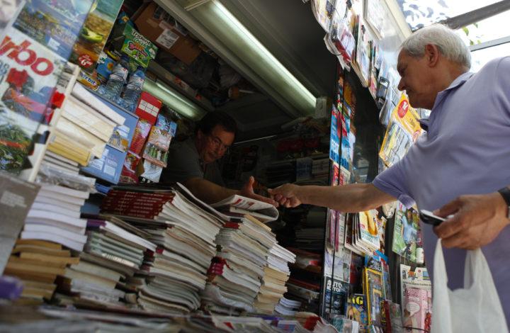 """Um popular compra os jornais num quiosque de venda de revistas e jornais, em Lisboa, 13 de julho de 2013. Nos últimos anos, na Avenida da Liberdade, em miradouros pelas sete colinas, nos jardins, à beira Tejo, nas praças, os quiosques foram nascendo ou ganhando vida """"como cogumelos"""" e, reinventando um centenário hábito lisboeta, puseram a cidade a mexer. (ACOMPANHA TEXTO). MIGUEL A. LOPES / LUSA"""