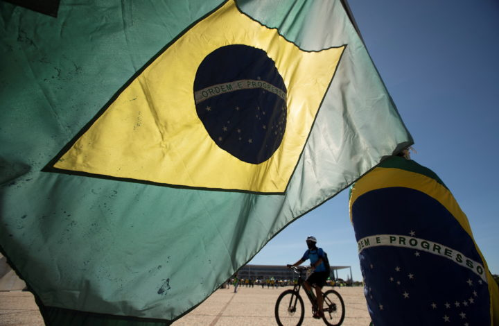 epaselect epa08456528 A supporter of Brazilian President Jair Bolsonaro waves a flag during a demonstration in Brasilia, Brazil, 31 May 2020. Brazilian President Jair Bolsonaro ignored on Sunday the seriousness of COVID-19, which already leaves almost 30 thousand deaths in the country, and attended a demonstration with thousands of people. The event took place at the gates of the Planalto Presidential Palace, and as has happened in demonstrations that 'Bolsonarism' held on recent Sundays, the people protested against Congress and the Supreme Court, which according to supporters of the extreme right's leader 'conspire' against the Government.  EPA/Joedson Alves